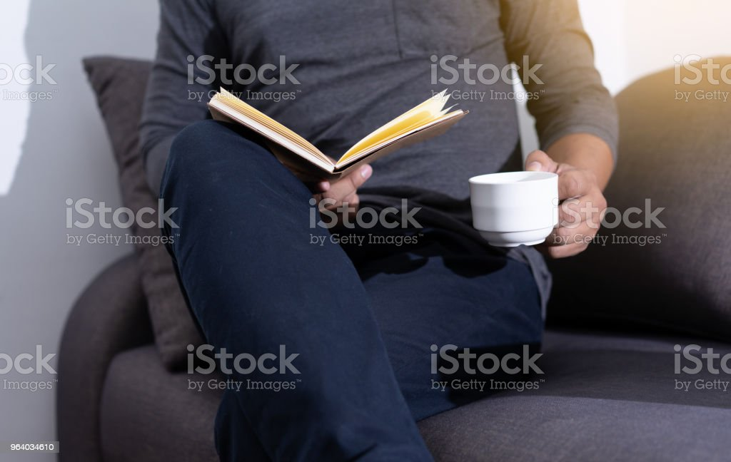 man reading a book and holding cup of coffee Sit Read Knowledge - Royalty-free Adult Stock Photo