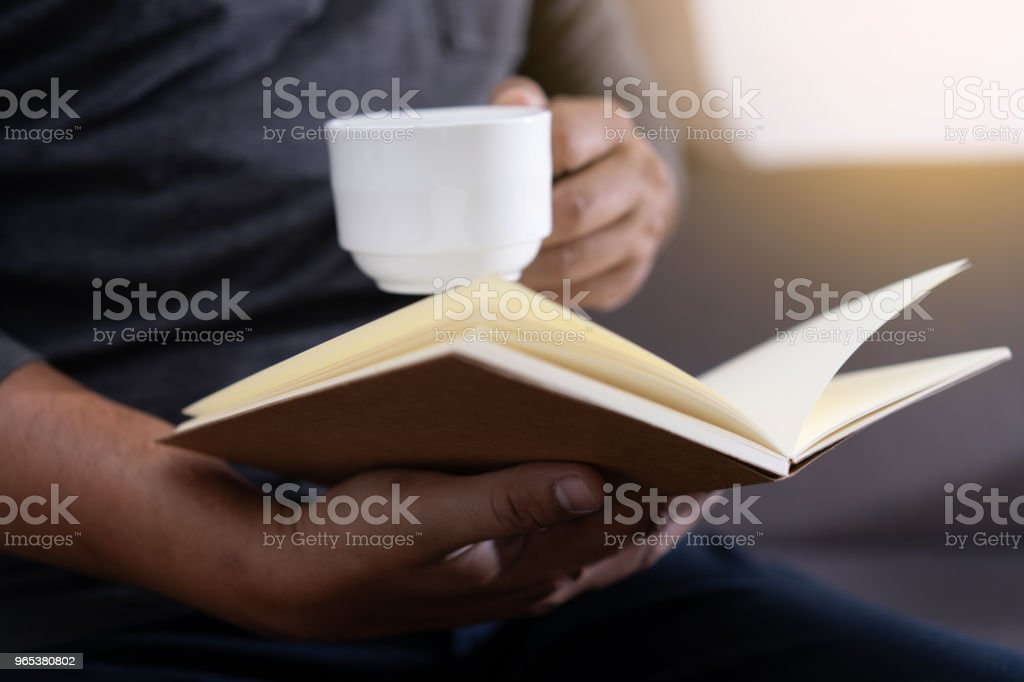 man reading a book and holding cup of coffee Sit Read Knowledge zbiór zdjęć royalty-free