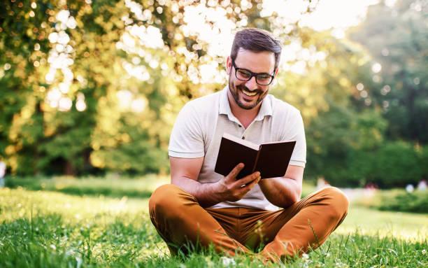 Mann liest ein Buch im Park. Bildung, Lifestyle-Konzept – Foto
