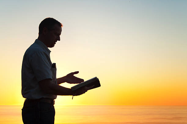 man reading a book of knowledge - preacher stock photos and pictures