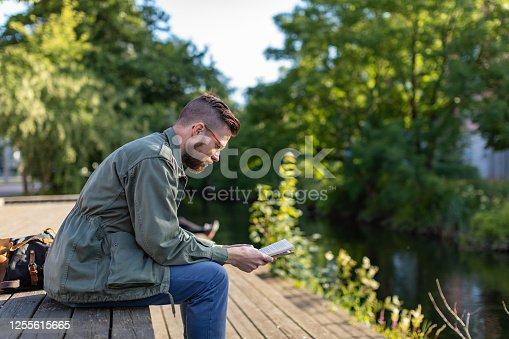 A man is reading a book by the water. He is wearing glasses and has a beard.