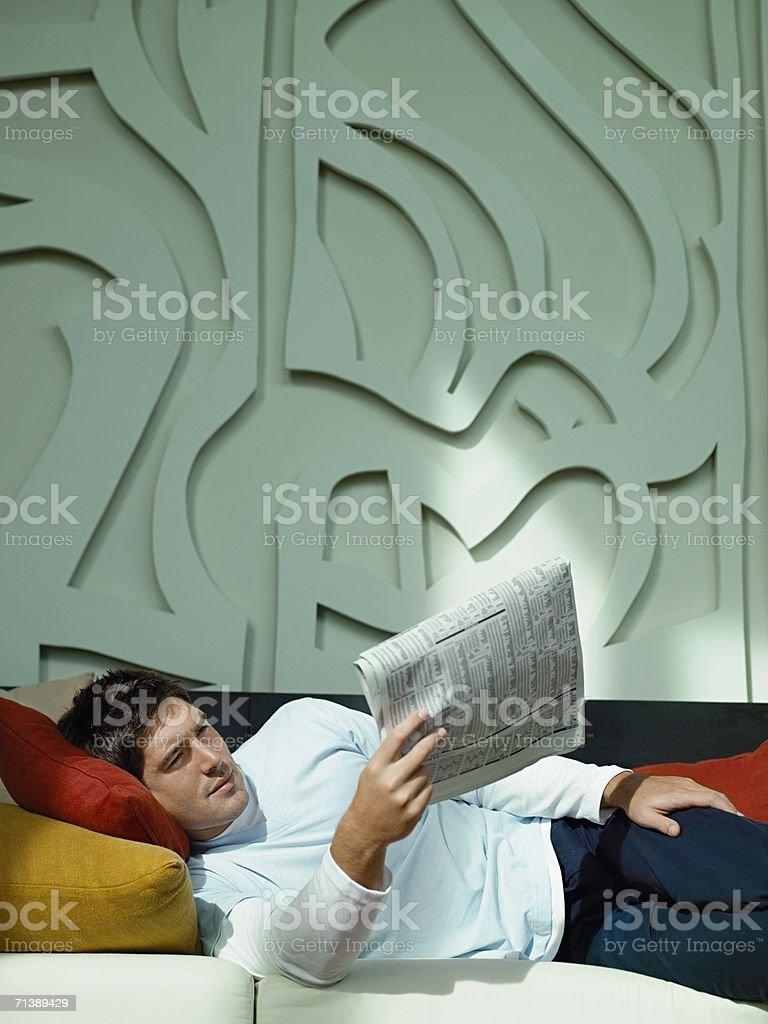 Man reading a newspaper on sofa royalty-free stock photo