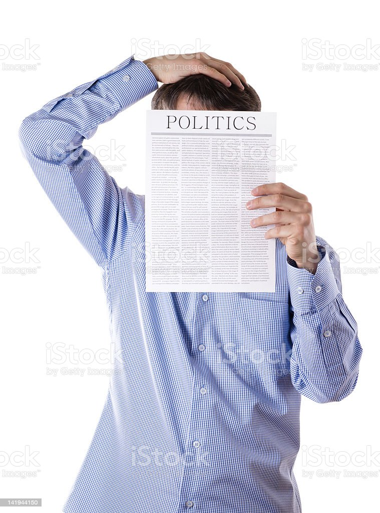 Man reading a newspaper with inscription POLITICS royalty-free stock photo
