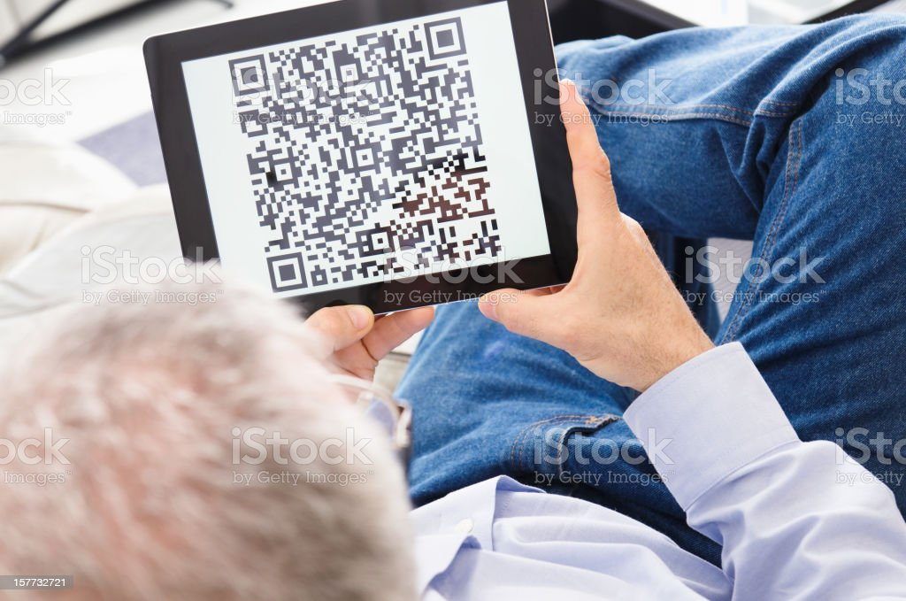 Man reading a qr code on digital tablet royalty-free stock photo