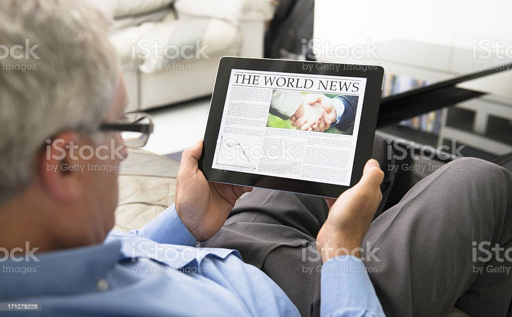 man reading  a World news newspaper on digital tablet royalty-free stock photo