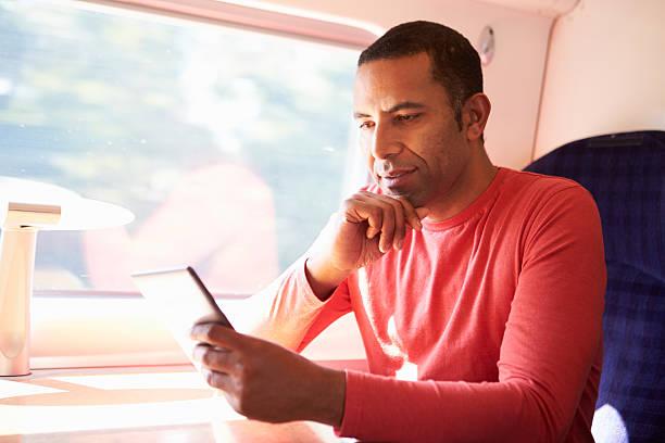 mann liest buch auf dem e - schnell lesen lernen stock-fotos und bilder
