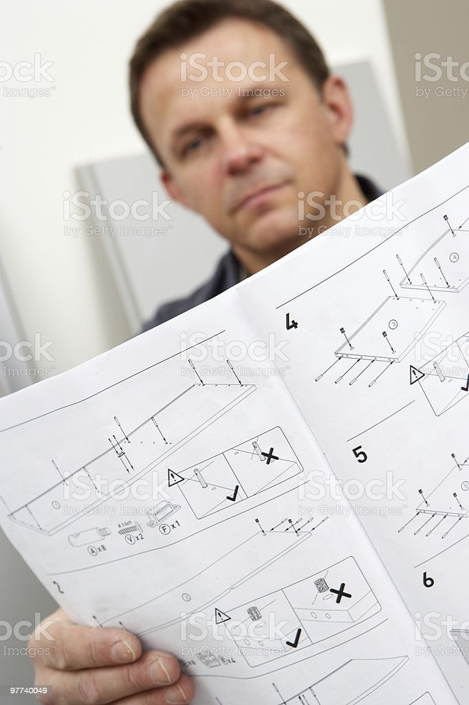 Man Reading Assembly Instructions For Furniture stock photo