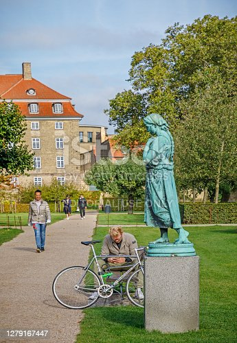 Kongens Have, Copenhagen, Denmark, September 26, 2020: Man reading behind a statue in a park in central Copenhagen
