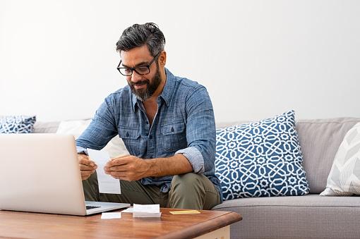 istock Man reading bills 1088347250