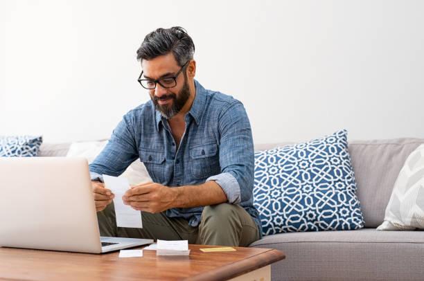 man reading bills - indian man stock photos and pictures