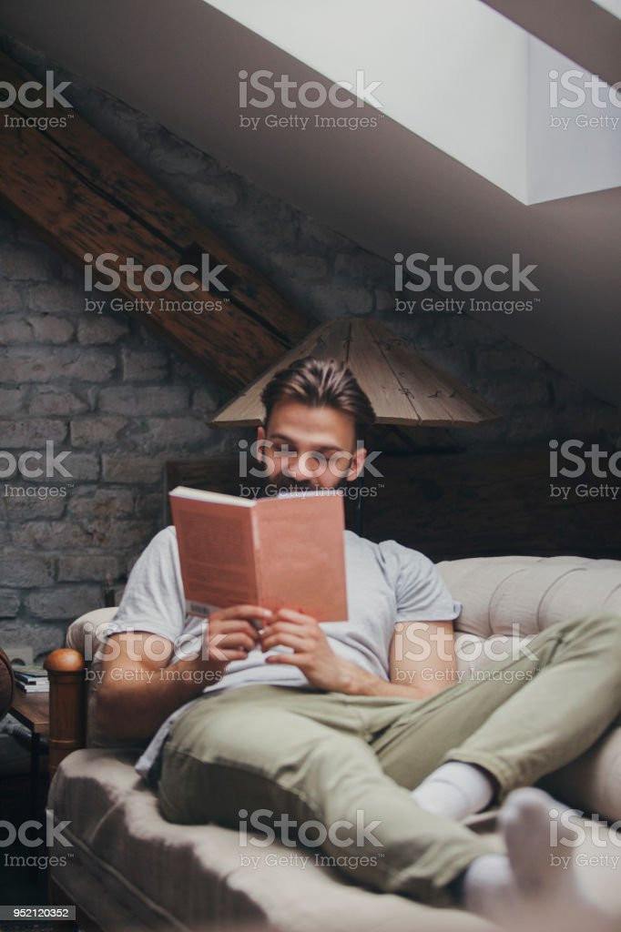 Man reading book at the sofa stock photo