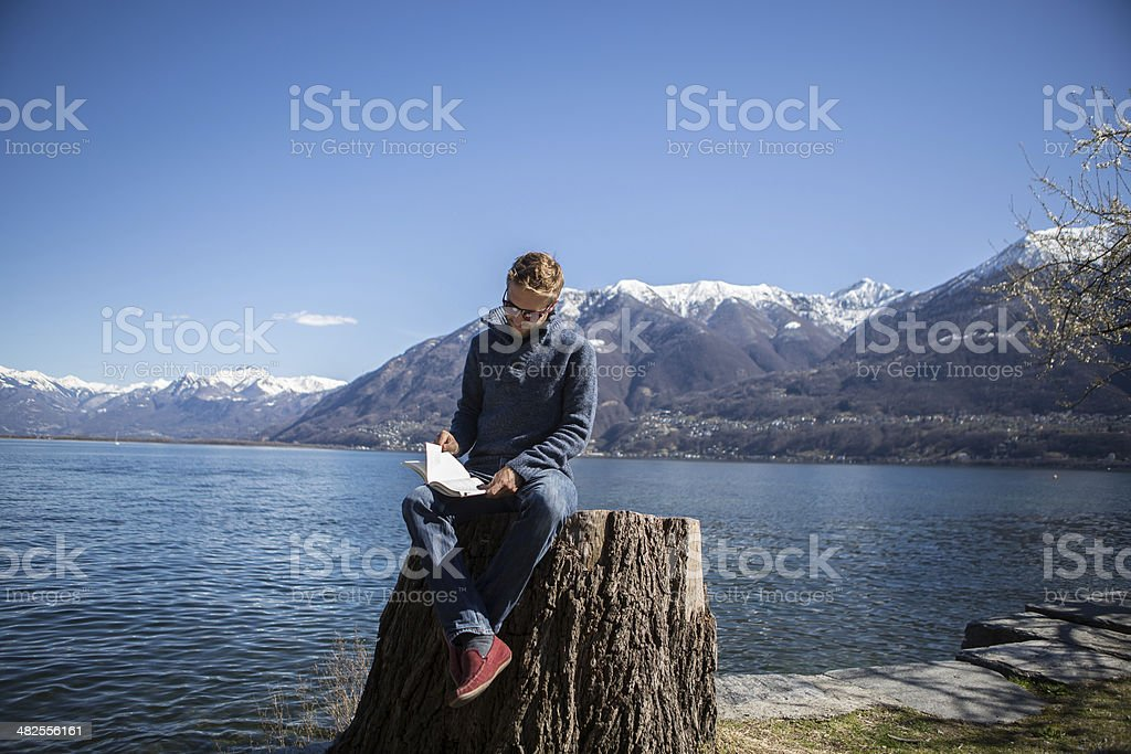 Man reading book by the lake stock photo