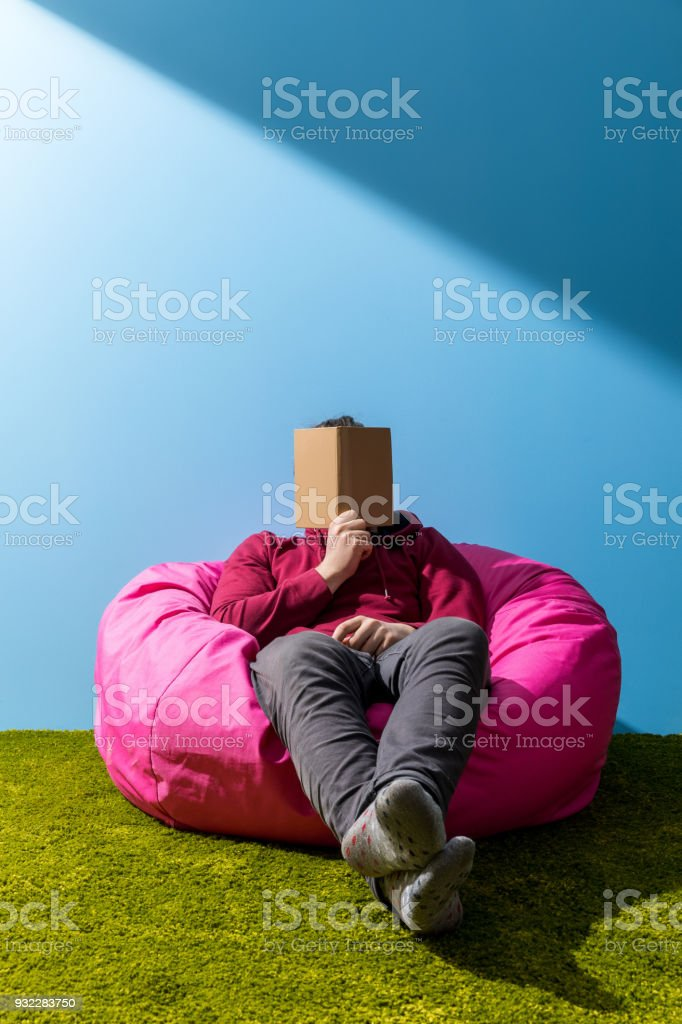 man reading book in bean bag in front of blue wall stock photo