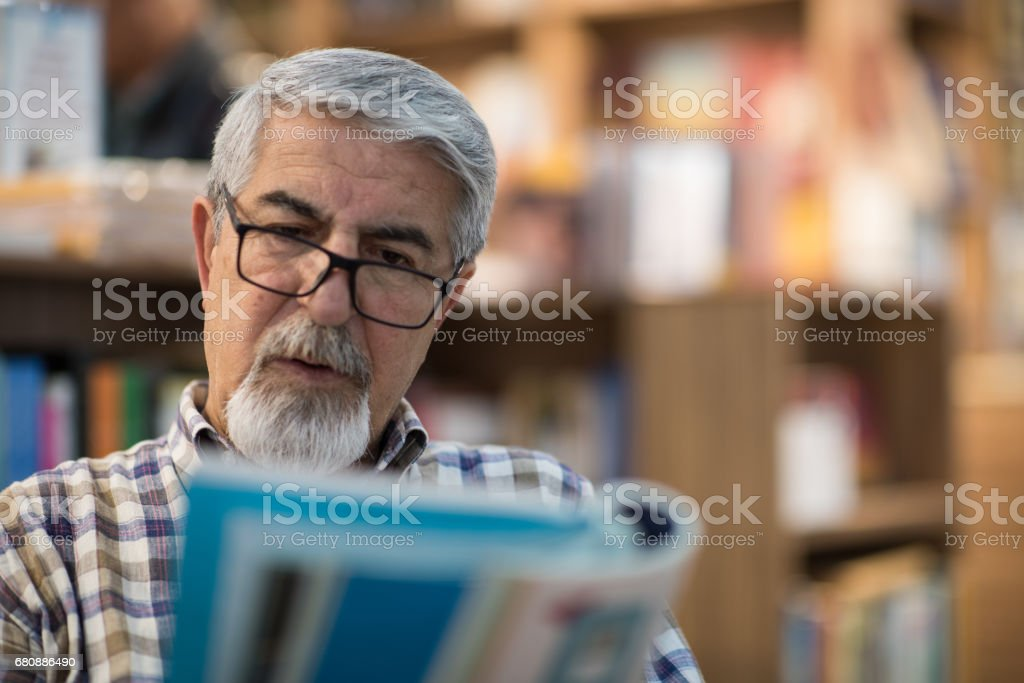 Man reading book in bookstore royalty-free stock photo