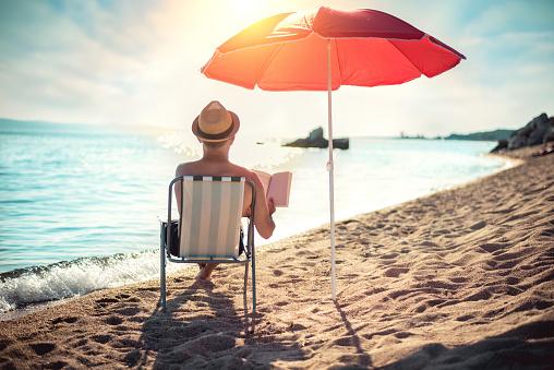 Man reading book in deck chair under sun umbrella near sea
