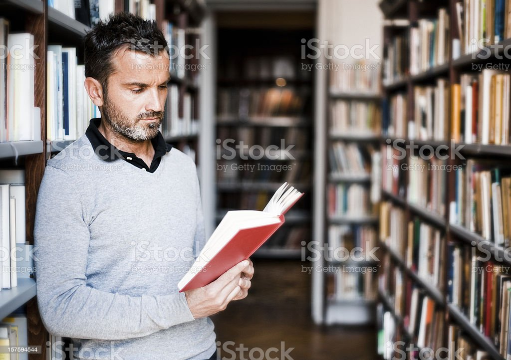 Man reading book in library isle royalty-free stock photo