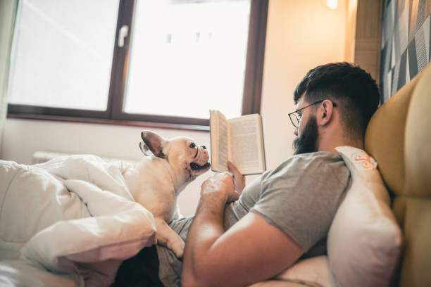 Mann liest Buch im Bett, kuschelt mit seinem Hund – Foto