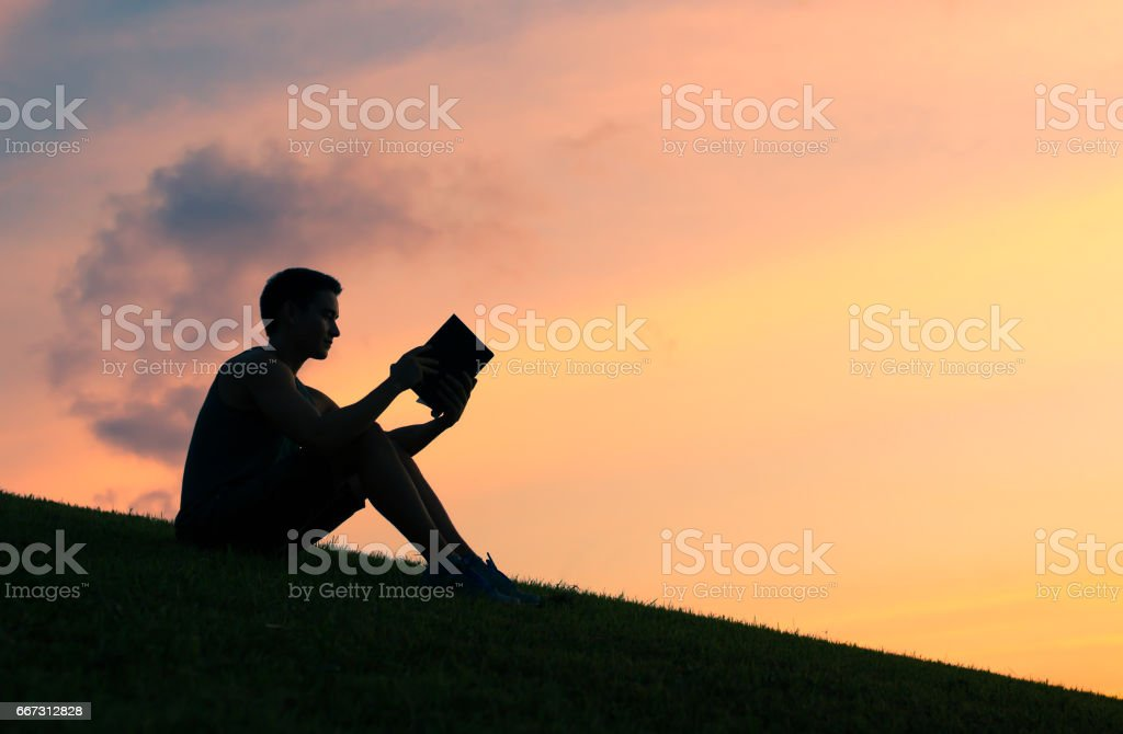 Man reading book in the park stock photo