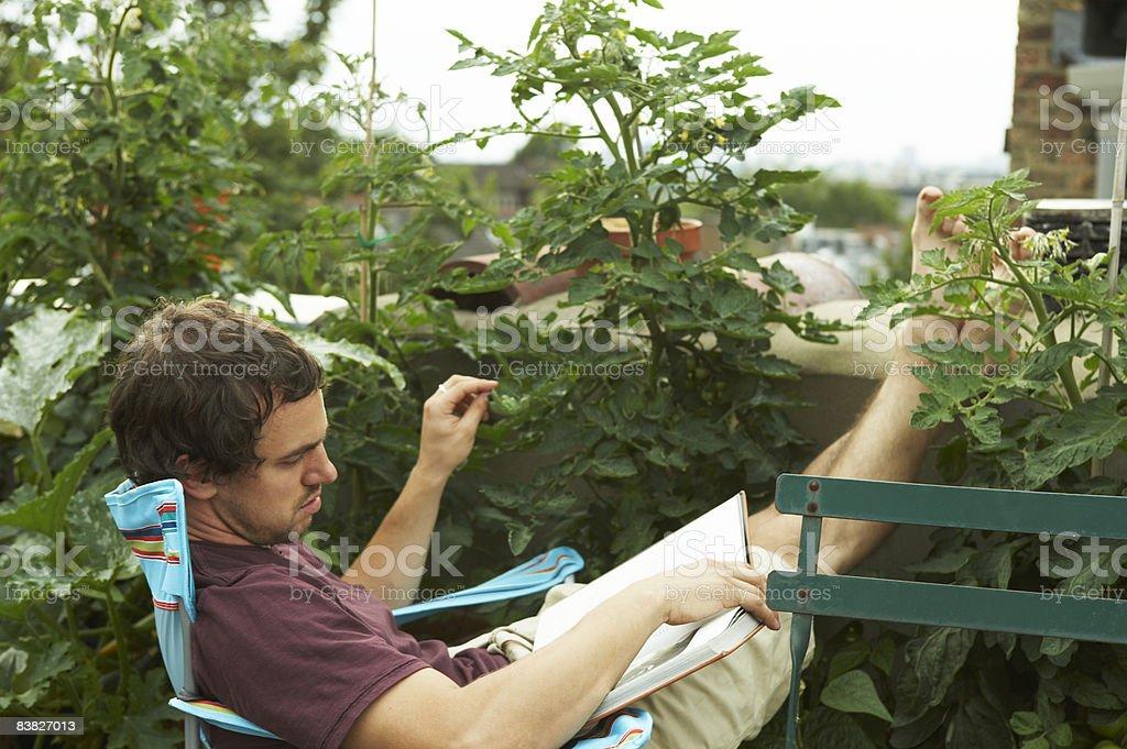 Homme lisant un livre sur la terrasse sur le toit photo libre de droits