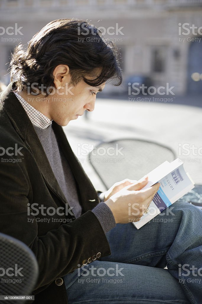 Man reading book outdoors royalty free stockfoto