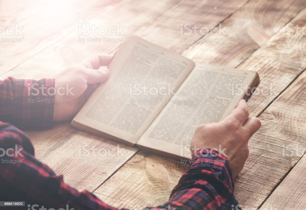 Man reading book sitting at a wooden table stock photo