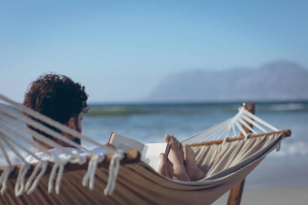 Mann liest Buch, während er auf Hängematte am Strand liegt – Foto