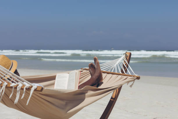 Man reading book while relaxing on hammock at beach stock photo