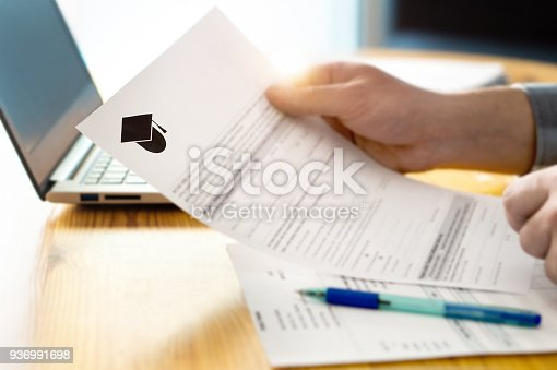 istock Man reading college or university application or document from school. College acceptance letter or student loan paper. 936991698