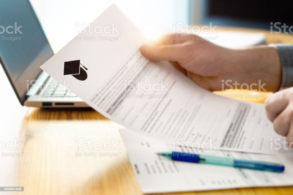Man reading college or university application or document from school. College acceptance letter or student loan paper. stock photo