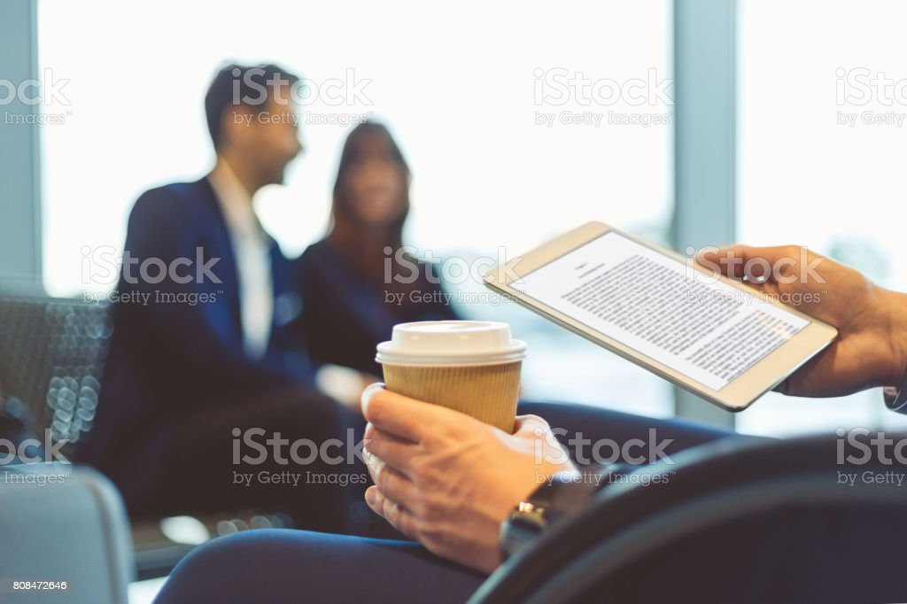 Man reading e-book in airport waiting area stock photo