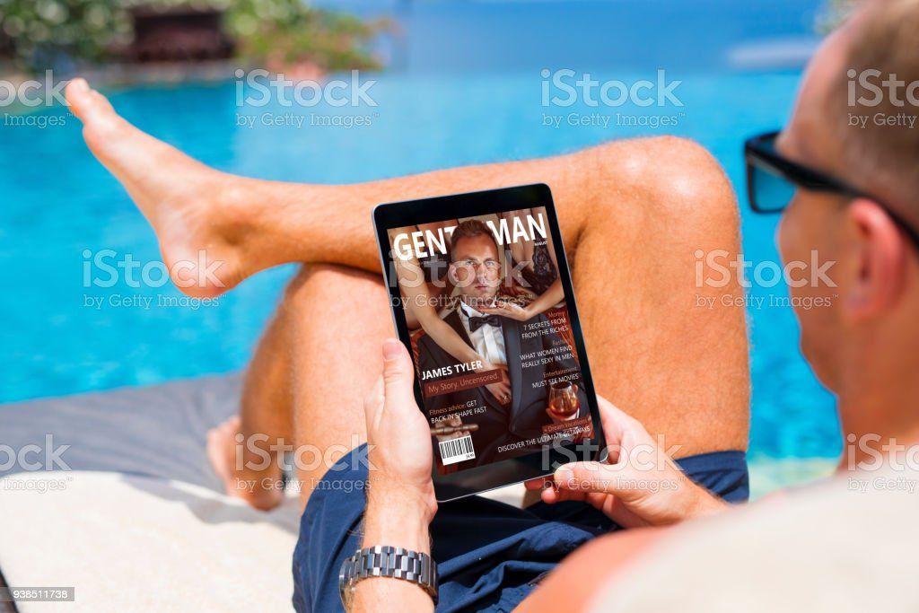 Man reading emagazine on vacation by the pool stock photo