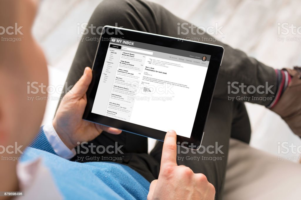 Man reading email on tablet stock photo