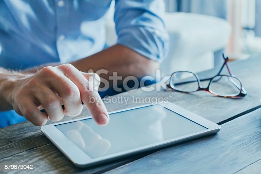istock man reading emails and news on social media 879879042