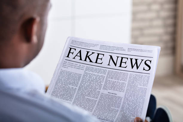 man reading fake news on newspaper - imitation stock pictures, royalty-free photos & images