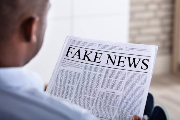 man reading fake news on newspaper - sztuczny zdjęcia i obrazy z banku zdjęć