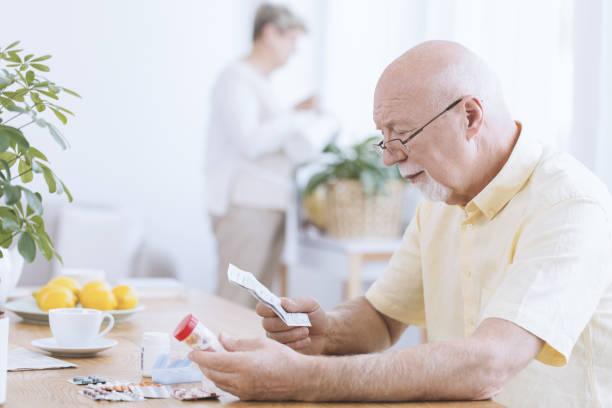 Man reading his medicines' prescription stock photo