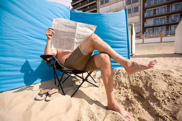 man reading his paper at the beach - newspaper beach stockfoto's en -beelden