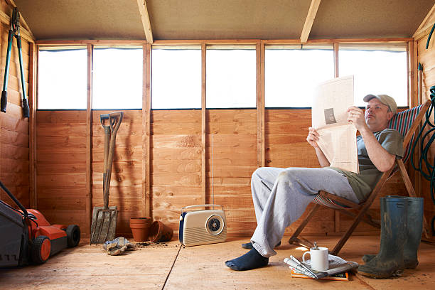 Man reading in garden shed stock photo