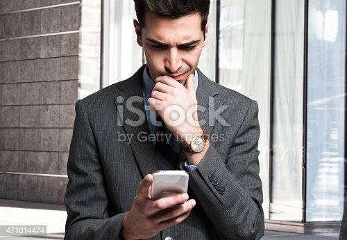 istock Man reading information on his cellular device 471014474