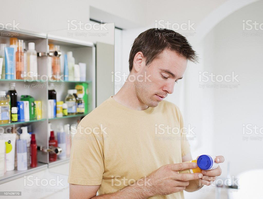 Man reading instructions on pill bottle stock photo
