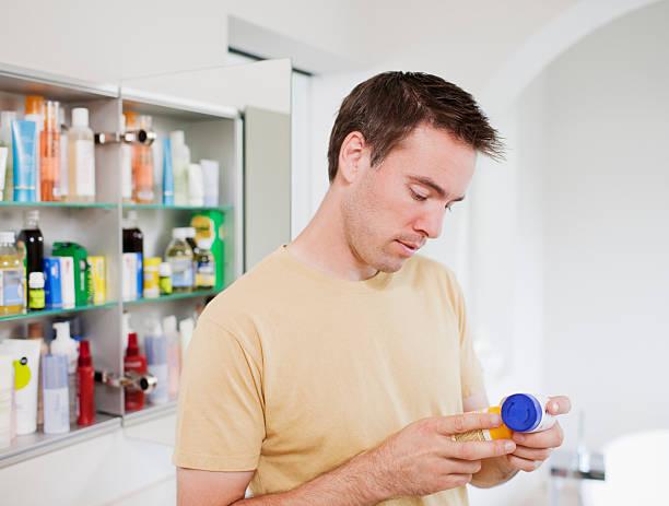 Man reading instructions on pill bottle stock photo