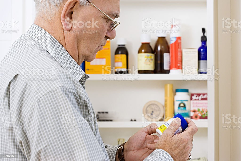 Man reading label on bottle of tablets stock photo