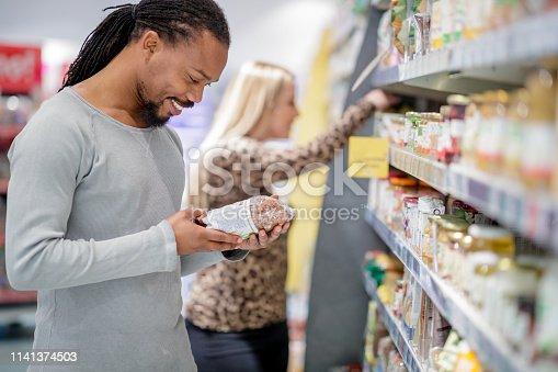 Black man reading label on organic cereals in supermarket