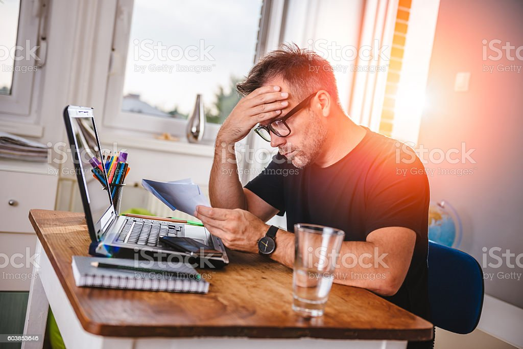Man reading letter and felling worried stock photo