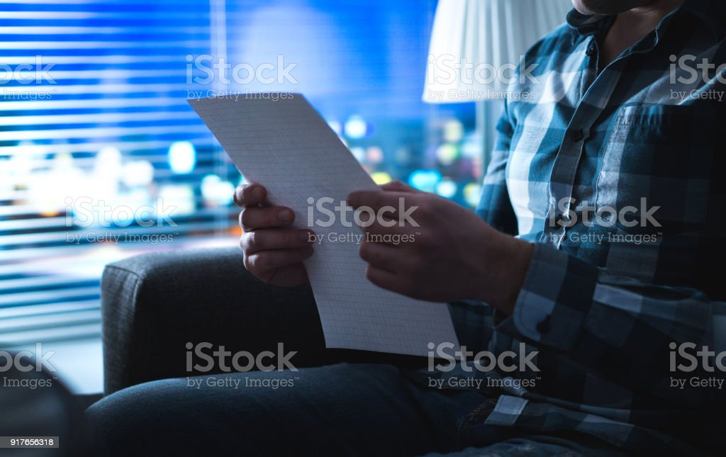Man reading letter in dark at night. Person writing note in shadows home by the window. Sudden inspiration or bad news. stock photo