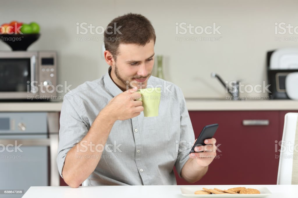 Man reading message on phone at breakfast stock photo