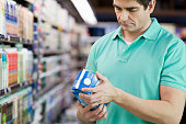 Man reading milk label in grocery store