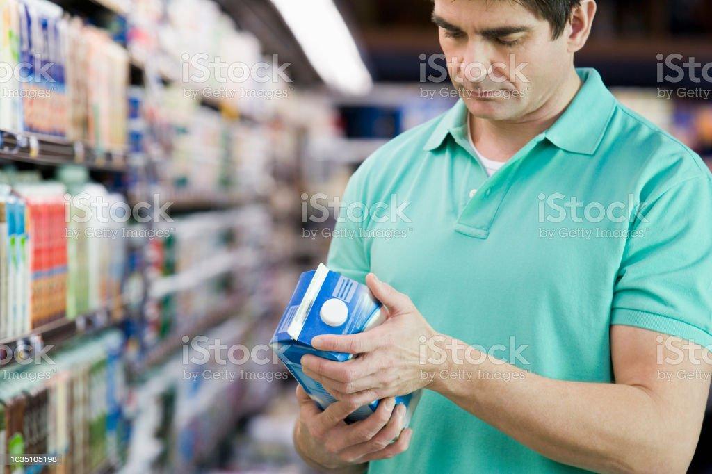 Mann liest Milch Label im Supermarkt – Foto
