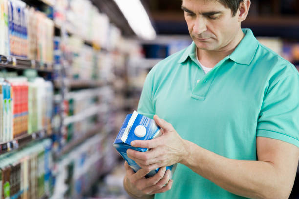 Man reading milk label in grocery store stock photo
