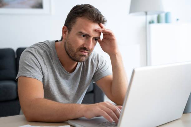Man reading negative news on his computer stock photo